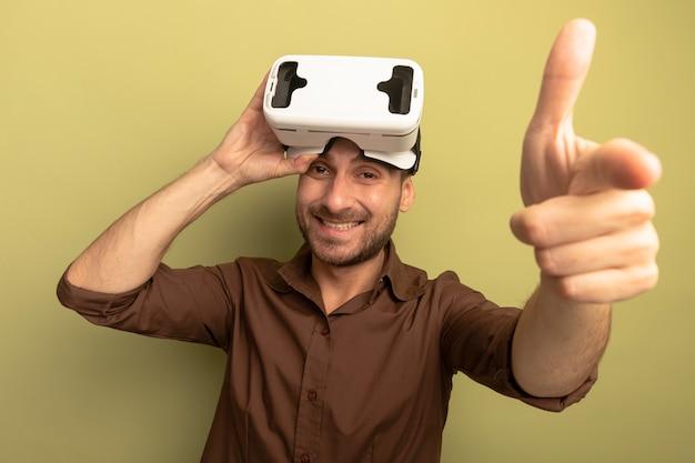 Glimlachende jonge blanke man met vr-headset op het hoofd grijpen het kijken en wijzen op camera geïsoleerd op olijfgroene achtergrond