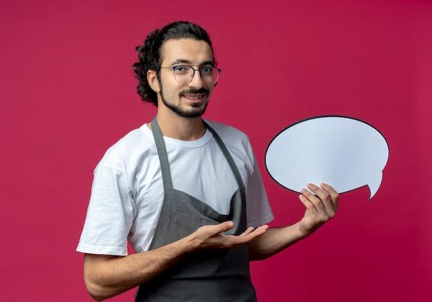 Glimlachende jonge blanke mannelijke kapper bril en golvende haarband dragen uniform houden praatjebel en wijzend met de hand naar het geïsoleerd op karmozijnrode achtergrond