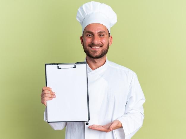 Glimlachende jonge blanke mannelijke kok in chef-kok uniform en pet met klembord wijzend erop