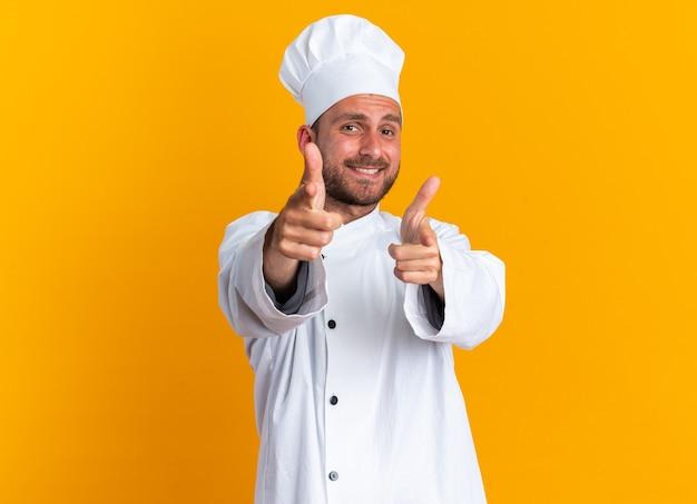 Glimlachende jonge blanke mannelijke kok in uniform van de chef-kok en pet die een pistoolgebaar doet
