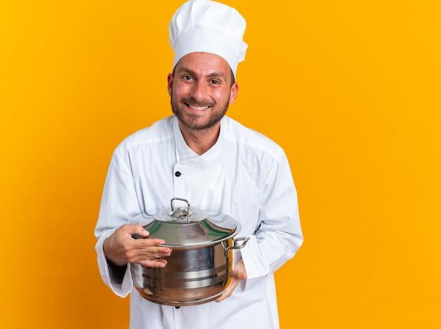 Glimlachende jonge blanke mannelijke kok in uniform van de chef-kok en pet met pot kijkend naar camera geïsoleerd op oranje muur met kopieerruimte