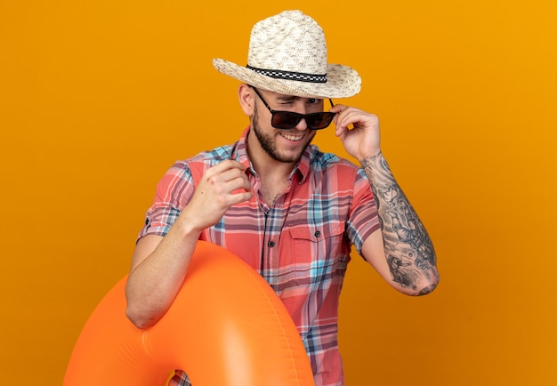 Glimlachende jonge blanke reiziger man met stro strand hoed in zonnebril knippert met zijn ogen en houdt zwemring geïsoleerd op oranje muur met kopieerruimte