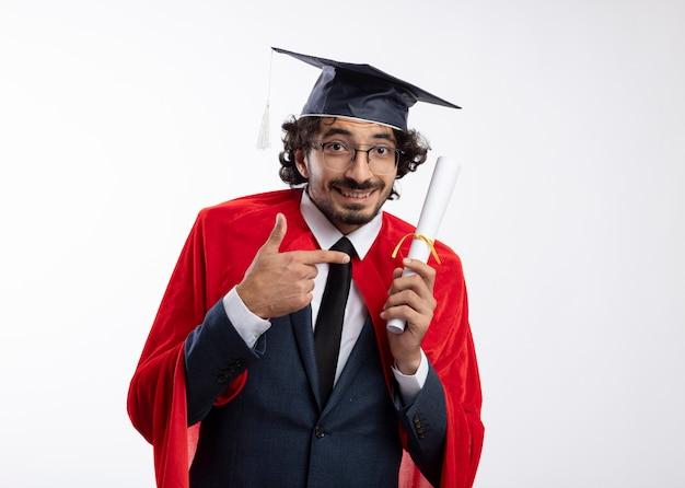 Glimlachende jonge blanke superheld man met optische bril in pak met rode mantel en afstudeerpet houdt vast en wijst naar diploma