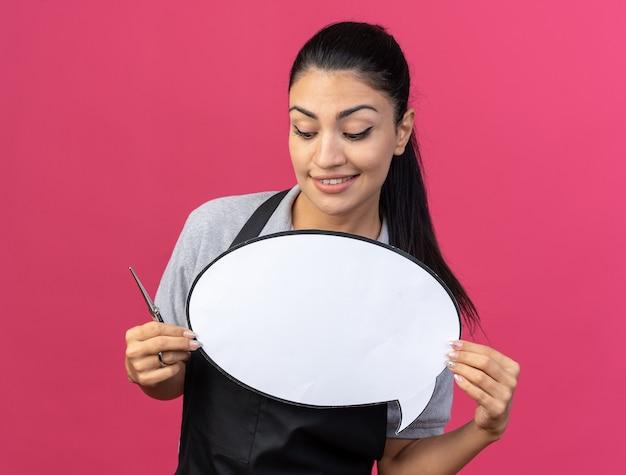 Glimlachende jonge blanke vrouwelijke kapper die uniform vasthoudt en naar tekstballon kijkt met een schaar in de hand geïsoleerd op roze muur