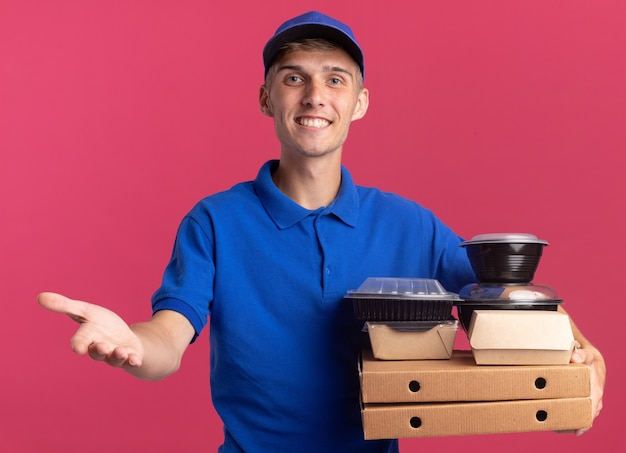 Glimlachende jonge blonde bezorger houdt hand open en houdt voedselcontainers en pakketten op pizzadozen geïsoleerd op roze muur met kopie ruimte