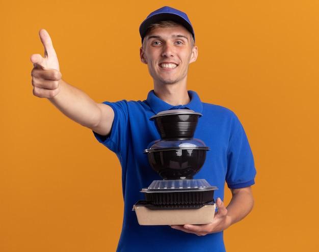 Glimlachende jonge blonde bezorger houdt voedselcontainers vast en wijst naar voren geïsoleerd op een oranje muur met kopieerruimte