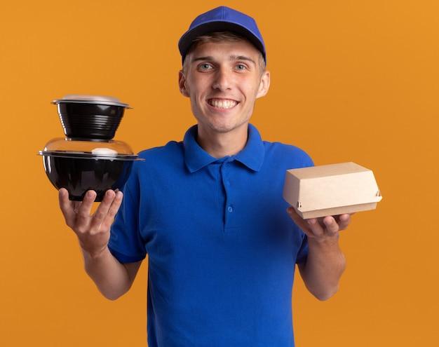 Glimlachende jonge blonde bezorger houdt voedselpakketten en containers vast