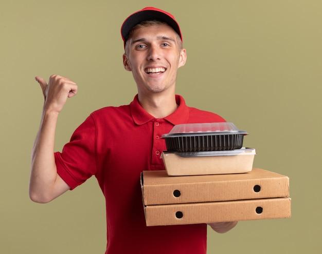 Glimlachende jonge blonde bezorger houdt voedselpakketten op pizzadozen en wijst aan de zijkant geïsoleerd op olijfgroene muur met kopieerruimte