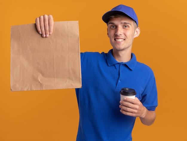 Glimlachende jonge blonde bezorger met papieren pakket en meeneemkop op sinaasappel