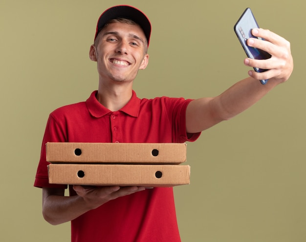 Glimlachende jonge blonde bezorger met pizzadozen en telefoon holding