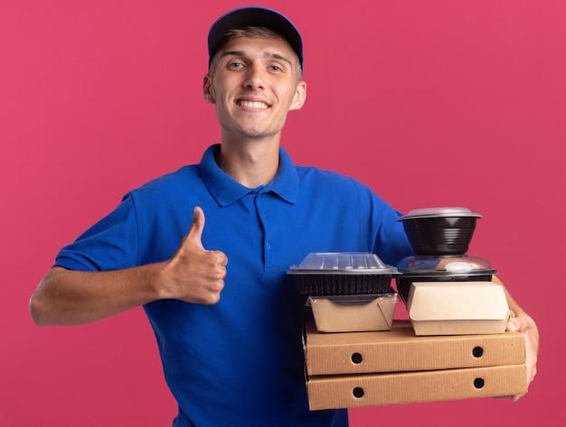 Glimlachende jonge blonde bezorger steekt zijn duim omhoog en houdt voedselcontainers en -pakketten op pizzadozen