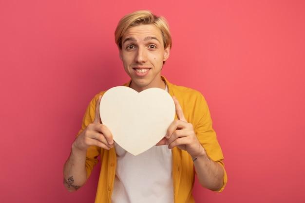 Glimlachende jonge blonde kerel die de gele doos van de het hartvorm van de t-shirtholding draagt