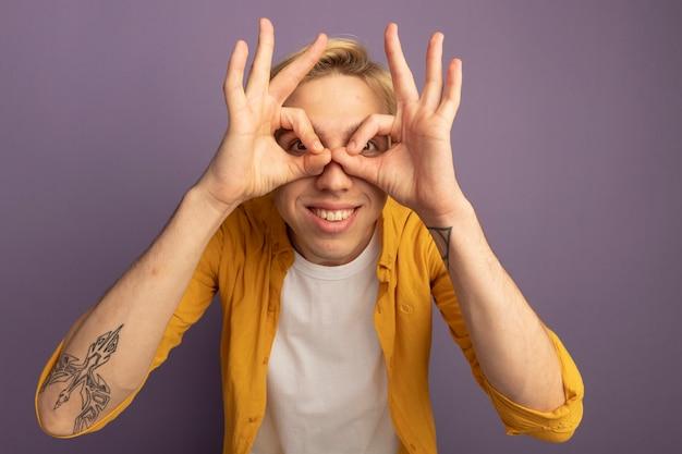 Glimlachende jonge blonde kerel die gele t-shirt draagt die blikgebaar toont dat op paars wordt geïsoleerd