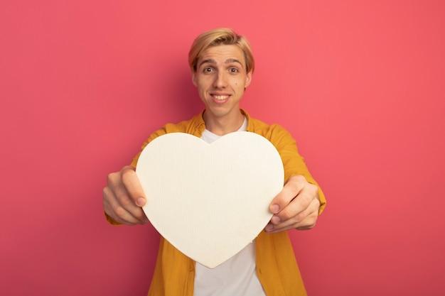 Glimlachende jonge blonde kerel die gele t-shirt draagt die de doos van de hartvorm standhoudt