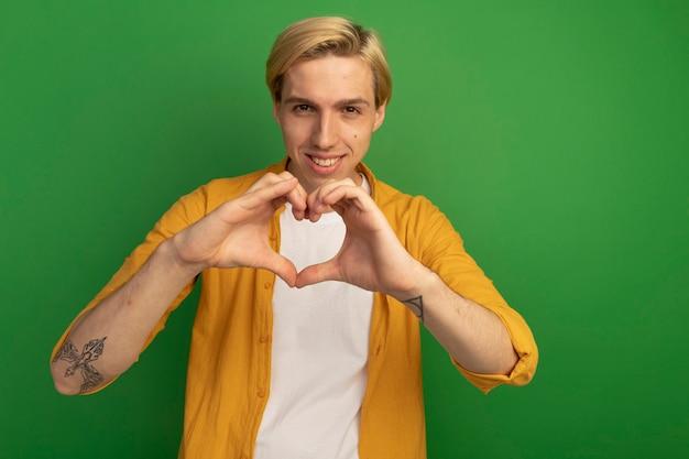 Glimlachende jonge blonde kerel die gele t-shirt draagt die hartgebaar toont dat op groen wordt geïsoleerd