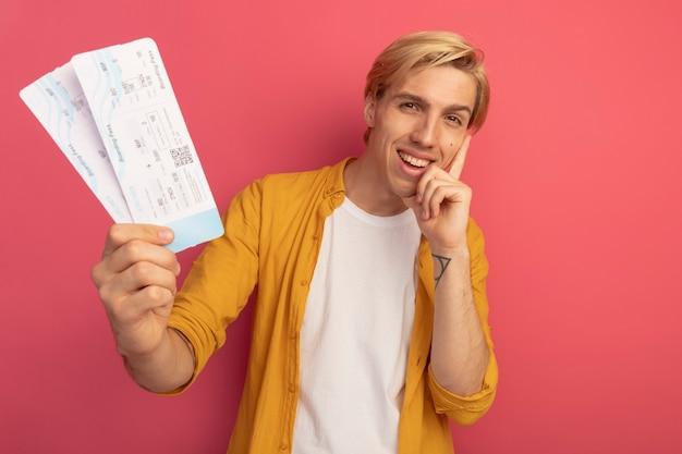 Glimlachende jonge blonde kerel die gele t-shirt draagt ?? die kaartjes houdt die hand op wang zetten die op roze met exemplaarruimte wordt geïsoleerd