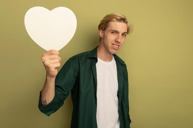 Glimlachende jonge blonde kerel die groene t-shirt draagt die de doos van de hartvorm opheft