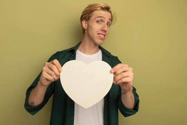 Glimlachende jonge blonde kerel die groene t-shirt draagt die de doos van de hartvorm standhoudt