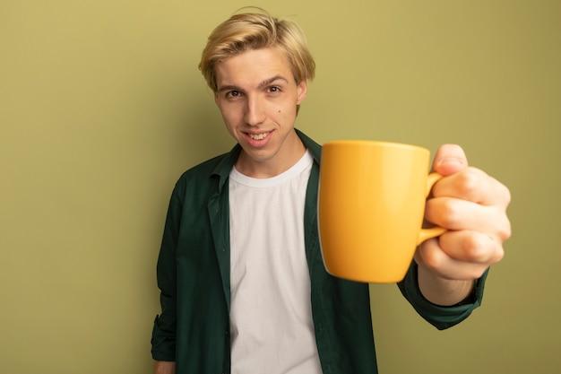 Glimlachende jonge blonde kerel die groene t-shirt draagt die kop thee standhoudt