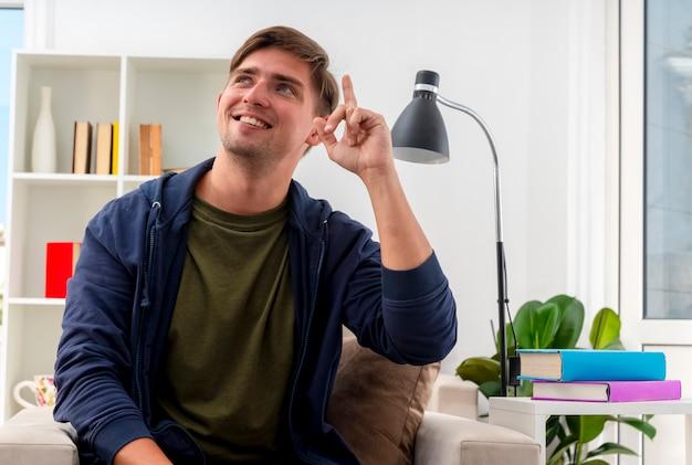 Glimlachende jonge blonde knappe man zit op fauteuil omhoog kijken naar kant in de woonkamer