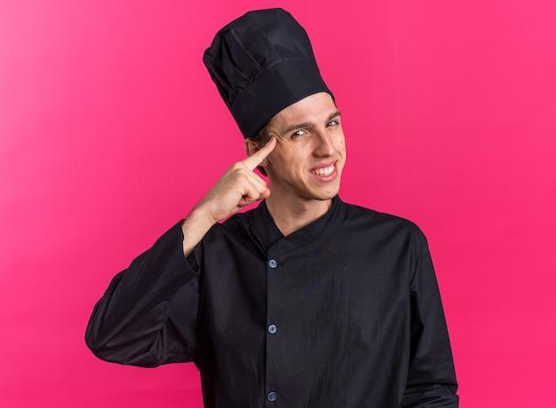 Glimlachende jonge blonde mannelijke kok in uniform van de chef-kok en pet die een denkgebaar doet