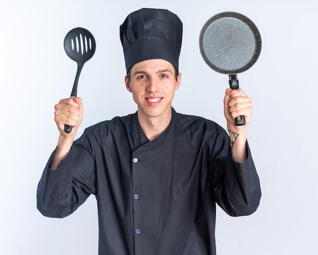 Glimlachende jonge blonde mannelijke kok in uniform van de chef-kok en pet kijkend naar camera met spatel en koekenpan geïsoleerd op een witte muur
