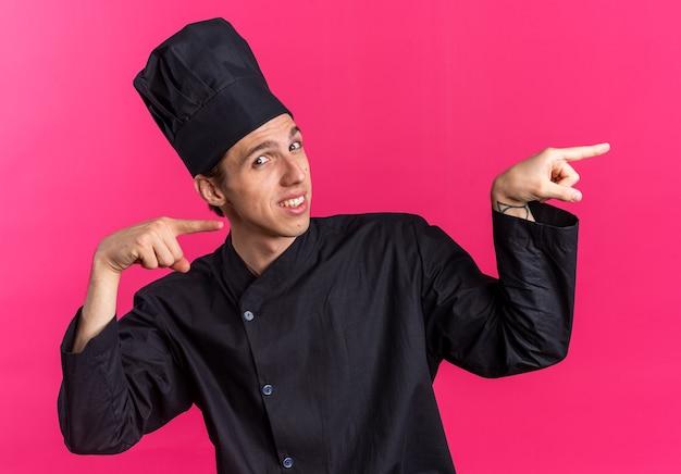 Glimlachende jonge blonde mannelijke kok in uniform van de chef-kok en pet kijkend naar camera wijzend naar kant geïsoleerd op roze muur