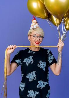 Glimlachende jonge blonde partijvrouw die glazen en verjaardag glb houdt die ballons bekijkt die voorzijde bekijkt die op purpere muur wordt geïsoleerd