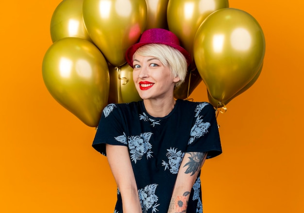 Glimlachende jonge blonde partijvrouw die partijhoed draagt die zich voor ballons bevindt die voorzijde bekijken die op oranje muur wordt geïsoleerd