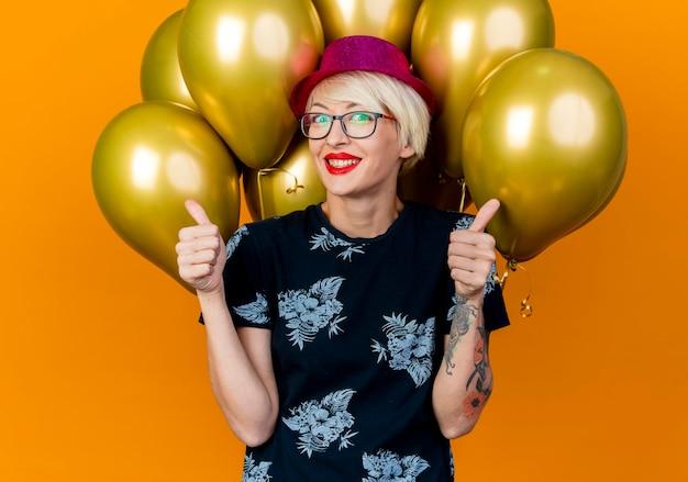 Glimlachende jonge blonde partijvrouw die partijhoed en glazen draagt die zich voor ballons bevinden die voorzijde bekijken tonen die omhoog op oranje muur worden geïsoleerd
