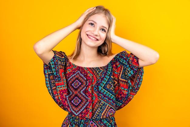 Glimlachende jonge blonde slavische vrouw die handen op haar hoofd zet en omhoog kijkt