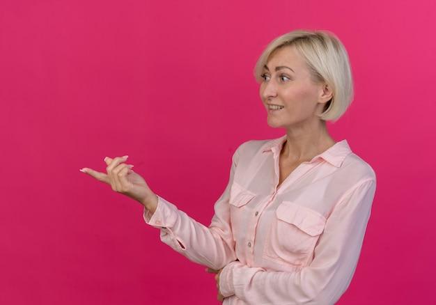Glimlachende jonge blonde slavische vrouw die zich in profielmening bevindt en recht omhoog kijkt richt geïsoleerd op roze achtergrond