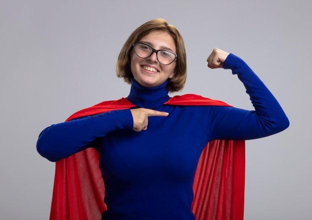 Glimlachende jonge blonde superheldenvrouw in rode cape die glazen dragen die sterk gebaar doen die voorzijde bekijken die op haar spieren wijzen die op witte muur worden geïsoleerd