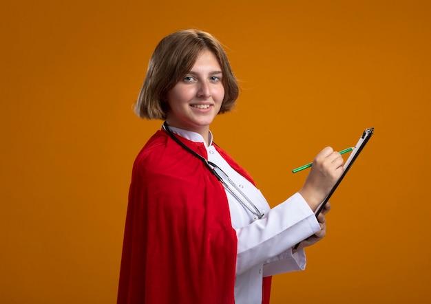 Glimlachende jonge blonde superheldvrouw in rode cape, doktersuniform en stethoscoop dragen, staande in profielweergave schrijven met potlood op klembord, geïsoleerd