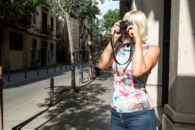 Glimlachende jonge blonde vrouw die foto's in de stad neemt