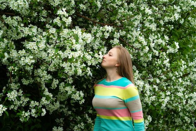 Glimlachende jonge blonde vrouw die geniet van de geur van appelboombloemen