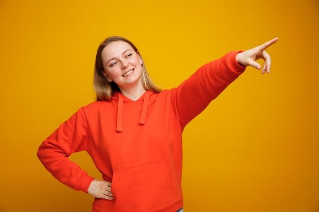 Glimlachende jonge blonde vrouw die hand op taille houdt die op hoek kijkt en benadrukt