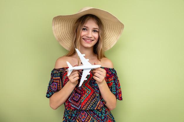 Glimlachende jonge blonde vrouw die met zonnehoed vliegtuigmodel houdt