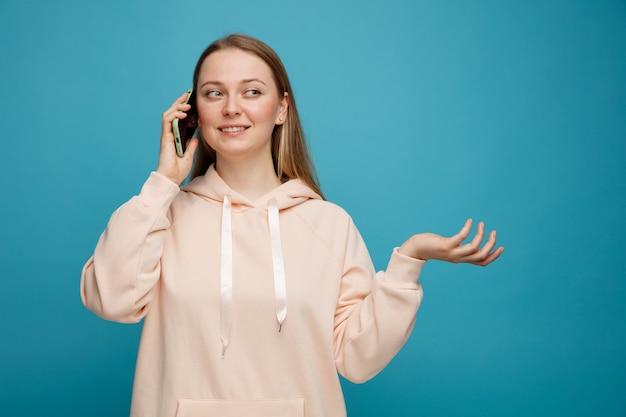 Glimlachende jonge blonde vrouw die op telefoon spreekt die kant bekijkt die lege hand toont
