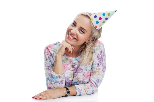 Glimlachende jonge blonde vrouw in een papieren pet. feestdagen en evenementen. geïsoleerd op een witte muur.
