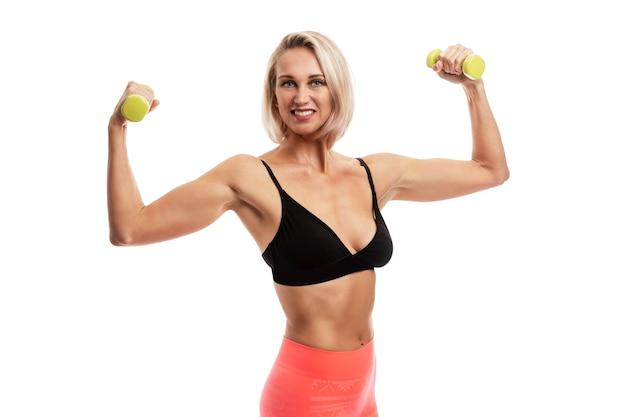 Glimlachende jonge blonde vrouw in sportkleding met halters in haar handen. sport als een manier van leven. geïsoleerd op een witte muur.