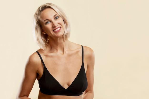 Glimlachende jonge blonde vrouw in zwarte sporttop.