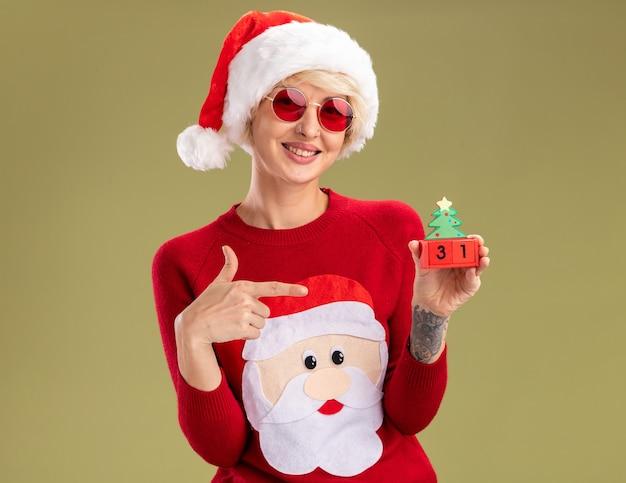 Glimlachende jonge blonde vrouw met kerstmuts en kersttrui van de kerstman met een bril die naar kerstboomspeelgoed wijst en naar een geïsoleerd op olijfgroene muur kijkt