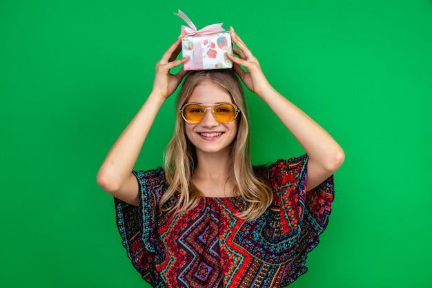 Glimlachende jonge blonde vrouw met zonnebril die een geschenkdoos boven haar hoofd houdt