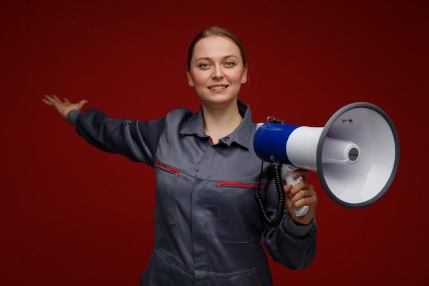 Glimlachende jonge blonde vrouwelijke ingenieur die eenvormige holdingsspreker draagt die erachter met hand richt