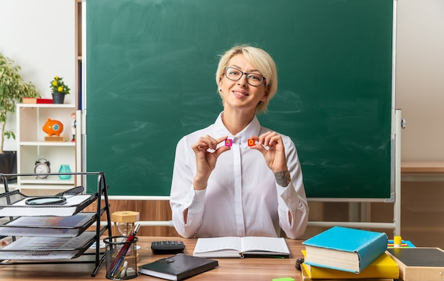 Glimlachende jonge blonde vrouwelijke leraar met een bril die aan het bureau zit met schoolbenodigdheden in de klas en naar de voorkant kijkt met kleine vierkante getallen vijf en nul