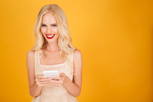 Glimlachende jonge blondevrouw die mobiele telefoon met behulp van.