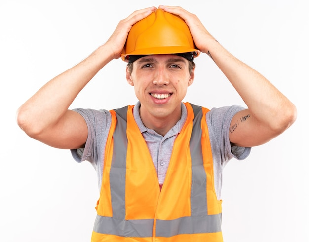 Glimlachende jonge bouwer man in uniform greep hoofd geïsoleerd op een witte muur