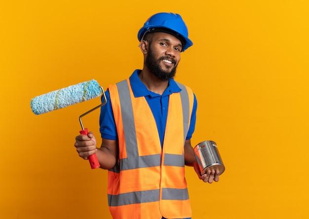 Glimlachende jonge bouwer man in uniform met veiligheidshelm met olieverf en verfroller geïsoleerd op oranje muur met kopieerruimte