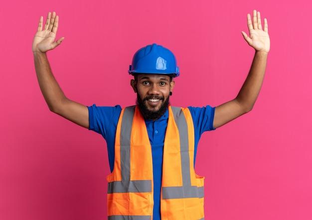 Glimlachende jonge bouwer man in uniform met veiligheidshelm staande met opgeheven handen geïsoleerd op roze muur met kopieerruimte